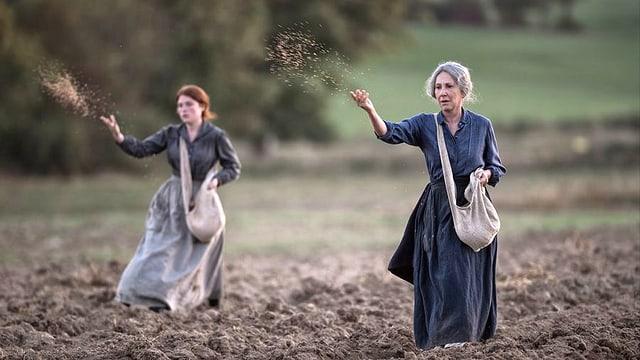 Zwei Frauen säen im Gleichschritt.