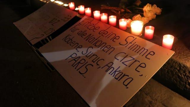 Gedenkkerzen und ein Plakat mit der Aufschrift: «Erhebe Deine Stimme für alle Nationen cizre, Kobane, Suruc, Ankara, Paris»