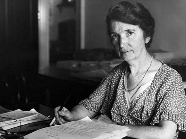 Schwarz-weiss-Bild einer Frau, die mit wachem Blick an einem Schreibtisch sitzt.