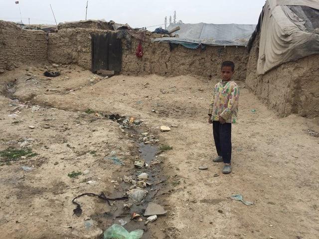 Ein Junge steht auf einem dreckigen Platz neben Lehmhütten.