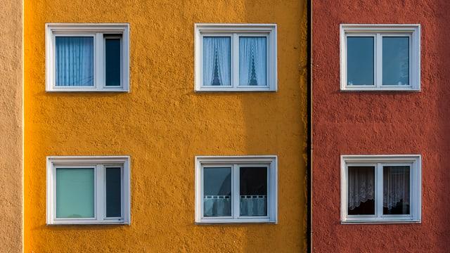 Blick auf eine gelbe Hauswand eines Wohnblocks. Zwei Stockwerke und 6 Fenster sind sichtbar.