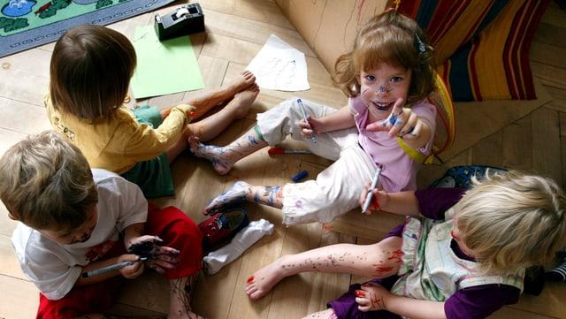 Kinder sitzen mit Buntstiften auf dem Boden.