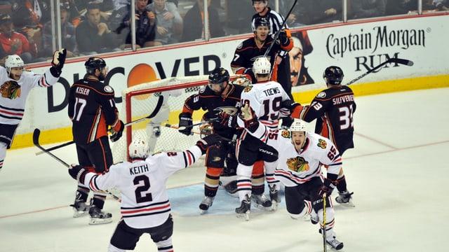 Vor einem Eishockeytor ist es zu einer Ansammlung von Spielern gekommen.