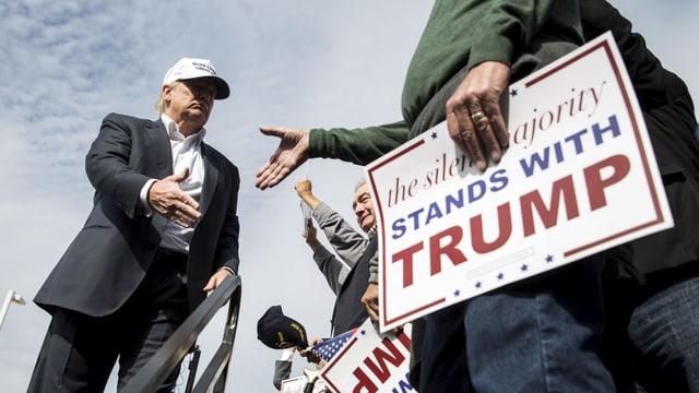 Trump mit weisser Baseballcap und Anzug schüttelt einem Anhänger die Hand, der ein Transparent hält mit der Aufschrift: «Die schweigende Mehrheit steht hinter Trump.»