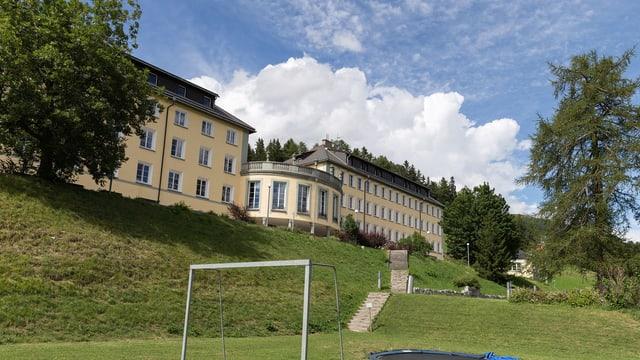 Das stattliche Schulgebäude in der grünen Landschaft an einem schönen Sommertag.