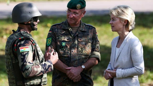 Ein Peschmerga-Kämpfer, ein deutscher Offizier und von der Leyen in einem Gespräch