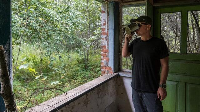 ein Mann trinkt Kaffee im Wald