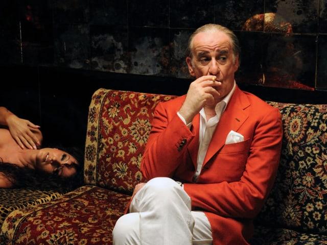 Ein elegant gekleideter Mann sitzt rauchend auf einem Sofa, neben ihm liegt eine nackte Frau.