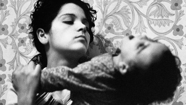 Libuna hält ein Mädchen im Arm