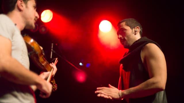 Ein Mann mit Geige und ein Mann, der klatscht, stehen auf einer rot beleuchteten Bühne und schauen sich an.