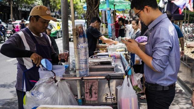 Ein Strassenverkäufer bereitet einem Kunden sein Essen zu.
