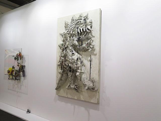 An einer weissen Wand hängen zwei Kunstwerke.