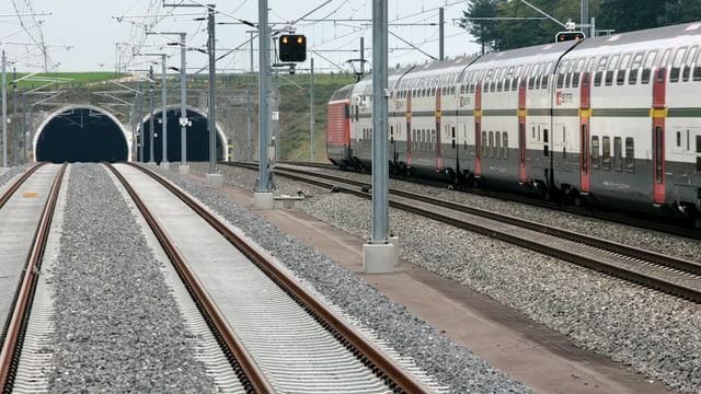 Eisenbahngeleise, die in zwei Tunnelportale führen, rechts davon ein Doppelstockzug der SBB