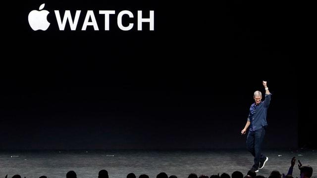 Vor dem Apple Watch Schriftzug hebt Tim Cook den Arm.