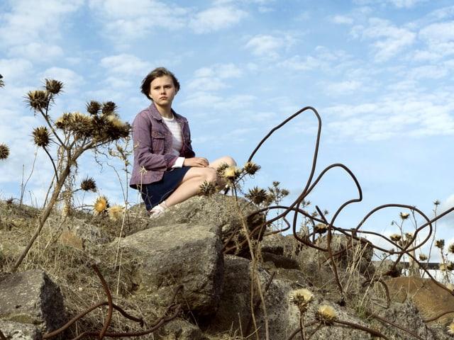 Ein Mädchen sitzt auf einem Stein in der Natur.