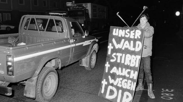 Ein Mann hält ein Plakat, auf dem «Unser Wald stirbt auch wegen dir!» steht, an einer Autostrasse.