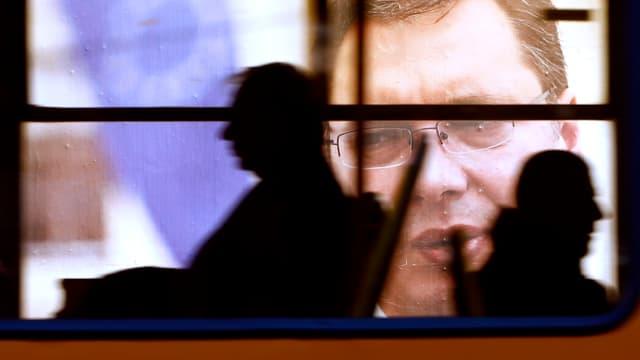 Ein Wahlplakat von Vucic fotografiert durch einen vorbeifahrenden Bus.