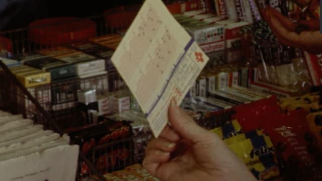Eine Person gibt einen Tippschein am Kiosk ab.