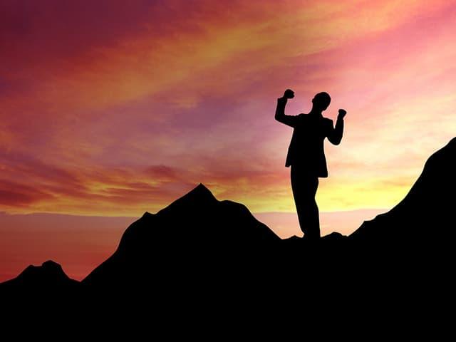Mit Blick auf einen Sonnenuntergang streckt ein Mann seine Arme in die Höhe.