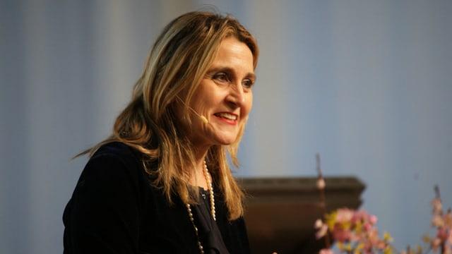 Eine Frau mit blonden Haaren lacht und spricht.