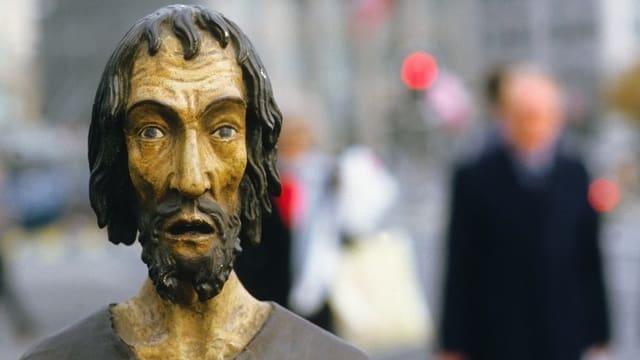Aus Holz geschnitzte Figur, die Bruder Klaus darstellt. Im Hintergrund verschwommene Strassenszene mit unerkennbaren Personen.