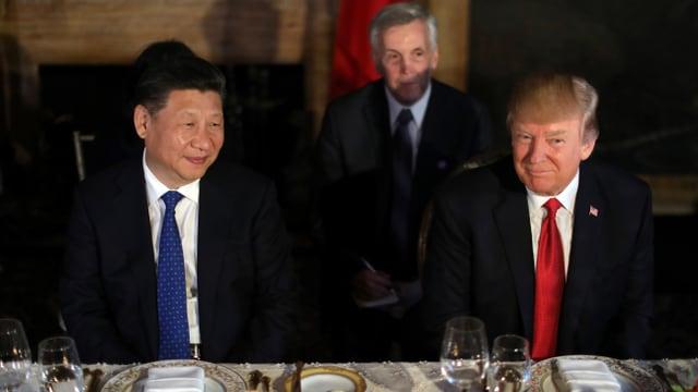 Xi Jinping und Donald Trump sitzen nebeneinander am Bankett-Tisch.