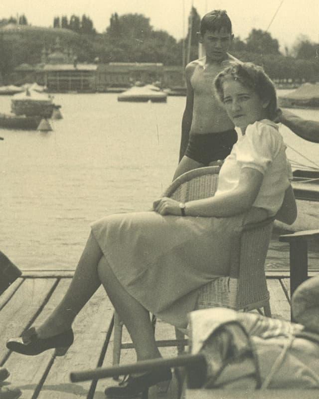 Alte Fotografie mit einer jungen Frau, die in einem Korbsessel sitzt.
