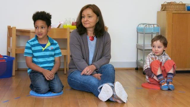 Zwei Kinder sitzen auf dem Boden auf einem Kissen, in der Mitte sitze die KIndergärtnerin. Alle schauen in eine Richtung und scheinen jemandem zuzuhören.