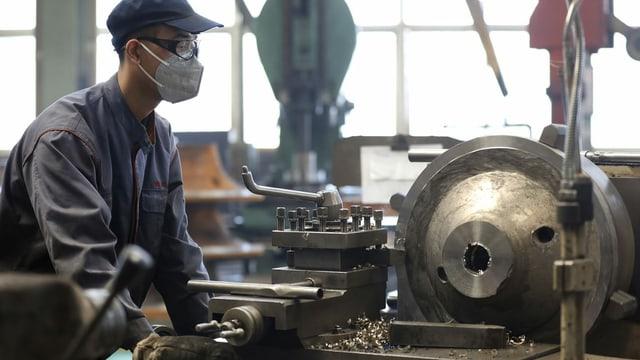 Ein Fabrikarbeiter an einer Maschine.