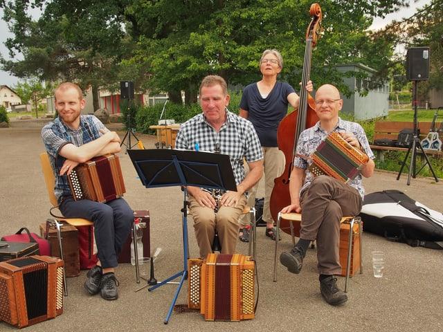 Drei Schwyzerörgeler und eine Kontrabassistin, die auf einem öffentlichen Platz spielen.