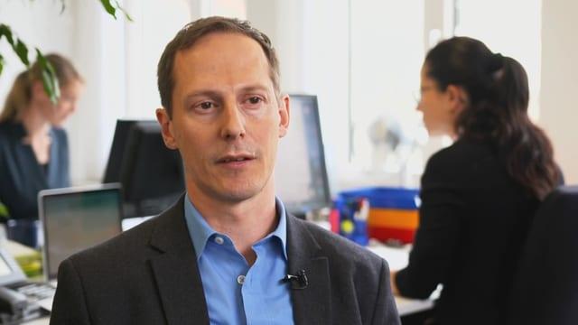 Ein Mann im schwarzen Kittel steht in einem Büro, hinter ihm sitzen zwei Frauen