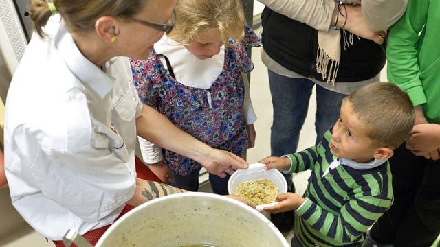 Flüchtlingskind bekommt einen Teller Essen.