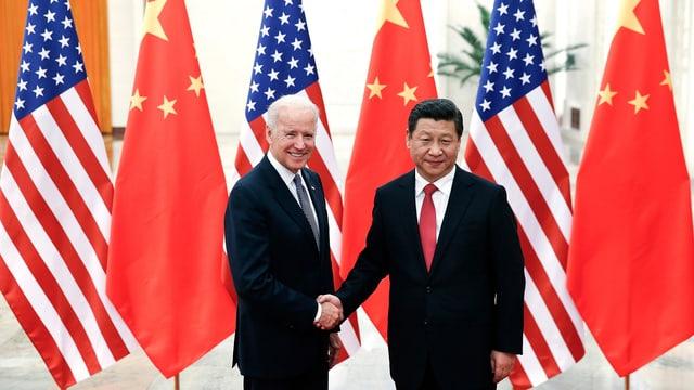 Biden und Xi geben sich vor chinesischen und amerikanischen Flaggen demonstrativ die Hand.
