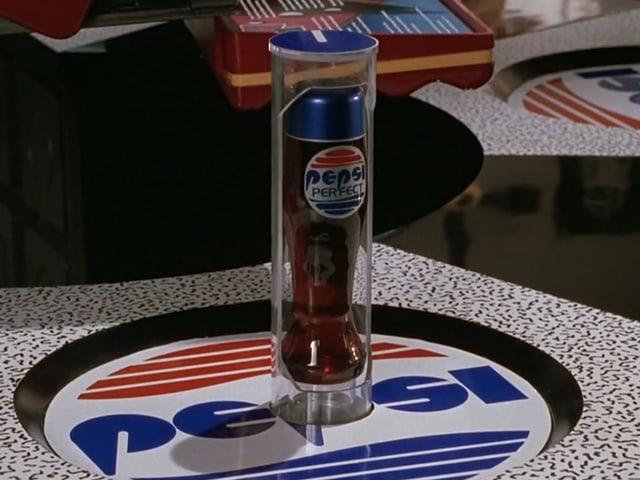 Tisch mit runder Unterlage, darauf der Schriftzug «Pepsi». Das Design sieht anders aus als das der richtigen Firma.