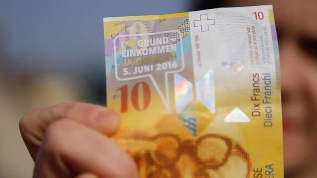 Eine Zehn-Franken-Note mit einem Aufkleber für ein Ja zur Volksinitiative.