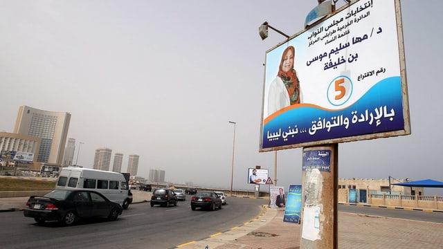 Autos fahren auf einer grossen Strasse an Wahlkampfplakaten vorbei
