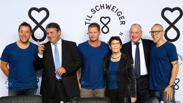 Sechs Personen stehen vor der Promotionswand der Stiftung