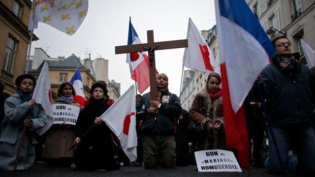 Demonstranten - darunter Kinder - protestieren mit Christus-Kreuz und Fahnen.