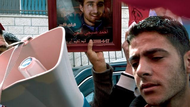 Mann mit Megafon vor einem Foto eines Gefallenen Palästinensers.