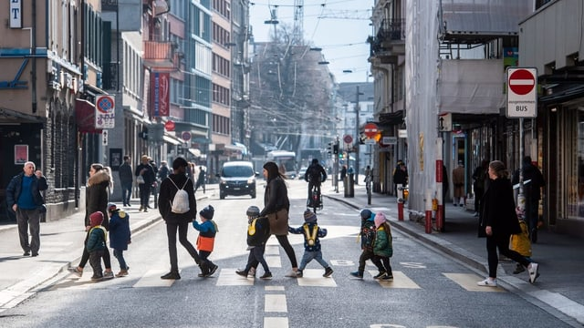 Eine Strasse an einem sonnigen Wintertag. Kinder gehen über einen Fussgängerstreifen.