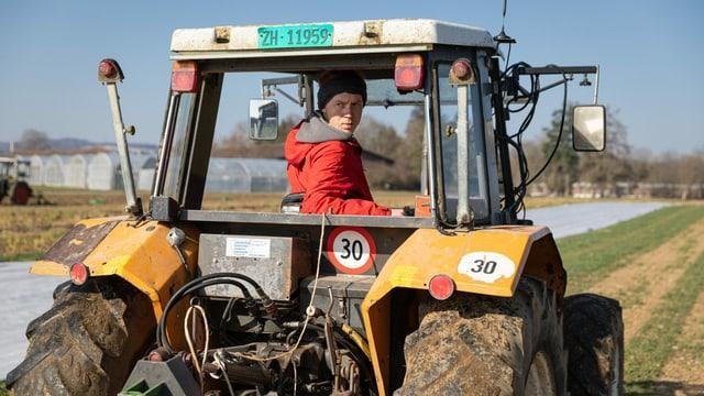 ein junger Mann fährt einen Traktor