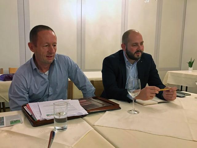 Zwei Männer sitzen hinter einem Tisch und geben eine Medienkonferenz.