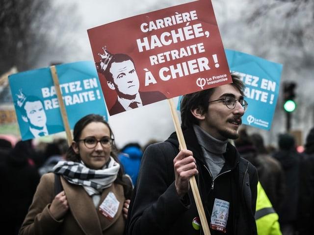 Ein Mann und eine Frau mit Bannern an einer Demonstration.