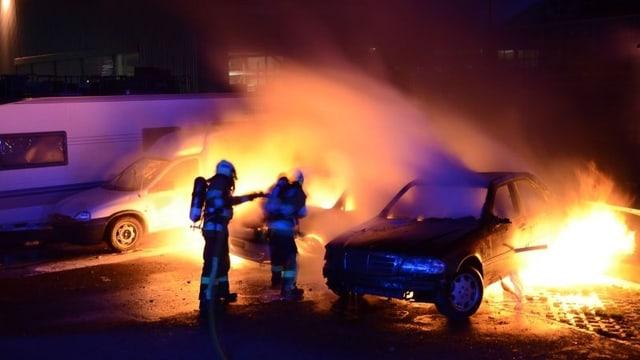 Zwei Feuerwehrmänner löschen zwei brennende Autos