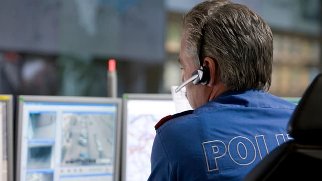 Polizist vor Computerbildschirm