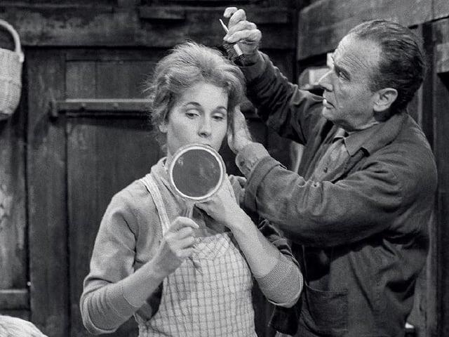 Frau mit Spiegel, Mann frisiert sie