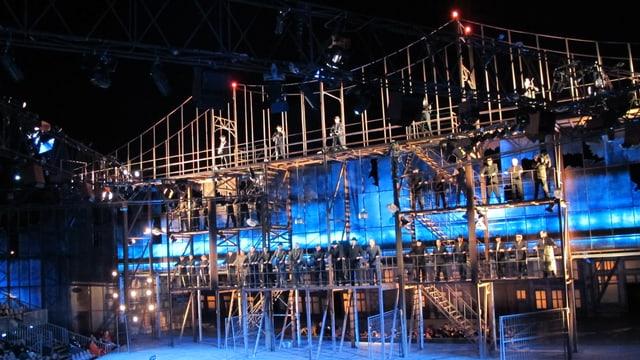 Schauspieler und Sänger auf einer nachgebauten Brooklyn Bridge, ein riesiges Bühnenbild im Rost-Look.