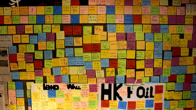 Ein Wand voller bunter Post-its mit chinesischen Schriftzeichen.