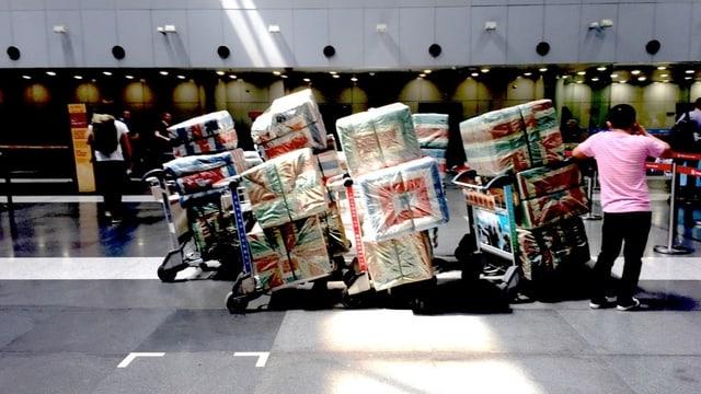 Mensch mit Gepäckwagen mit bunt eingepackter Schmuggelware