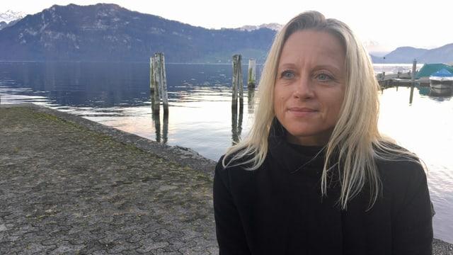 EIn Porträt einer Frau die am See sitzt.